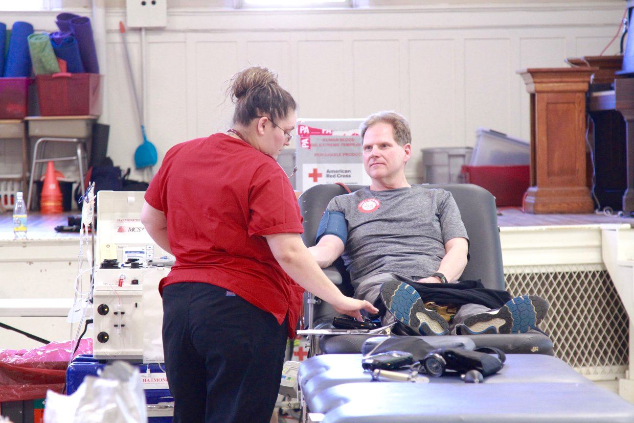 A man sits on a table giving blood while a nurse to the left of him monitors.