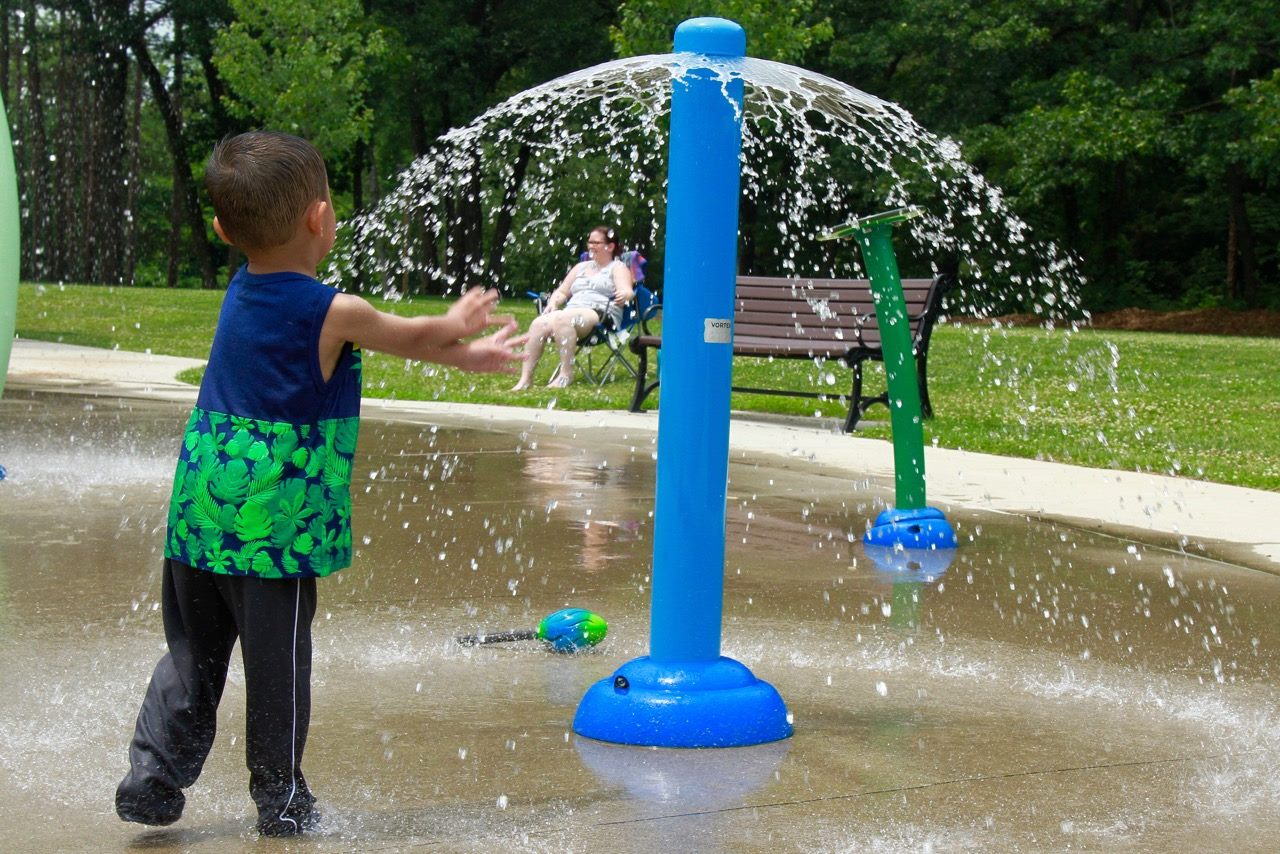 A small child runs toward a blue spray park bollard spraying water in a wide circle
