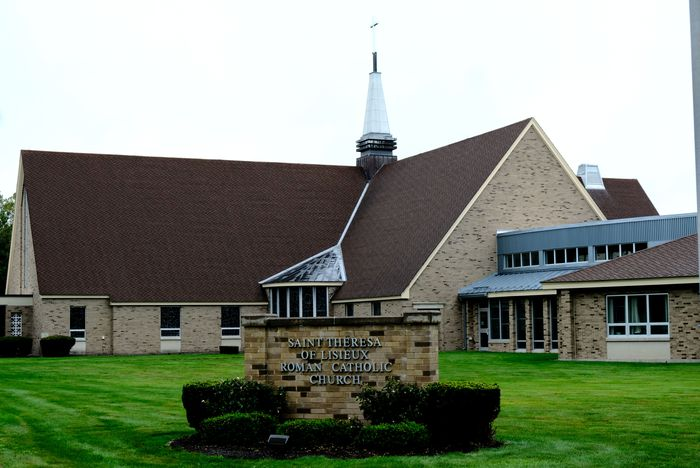 A beige brick church building with a steeple on top set back in green grass