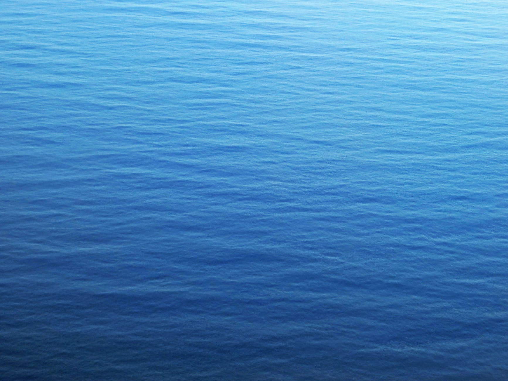 A blue, rippled body of water gradually changes to a lighter blue