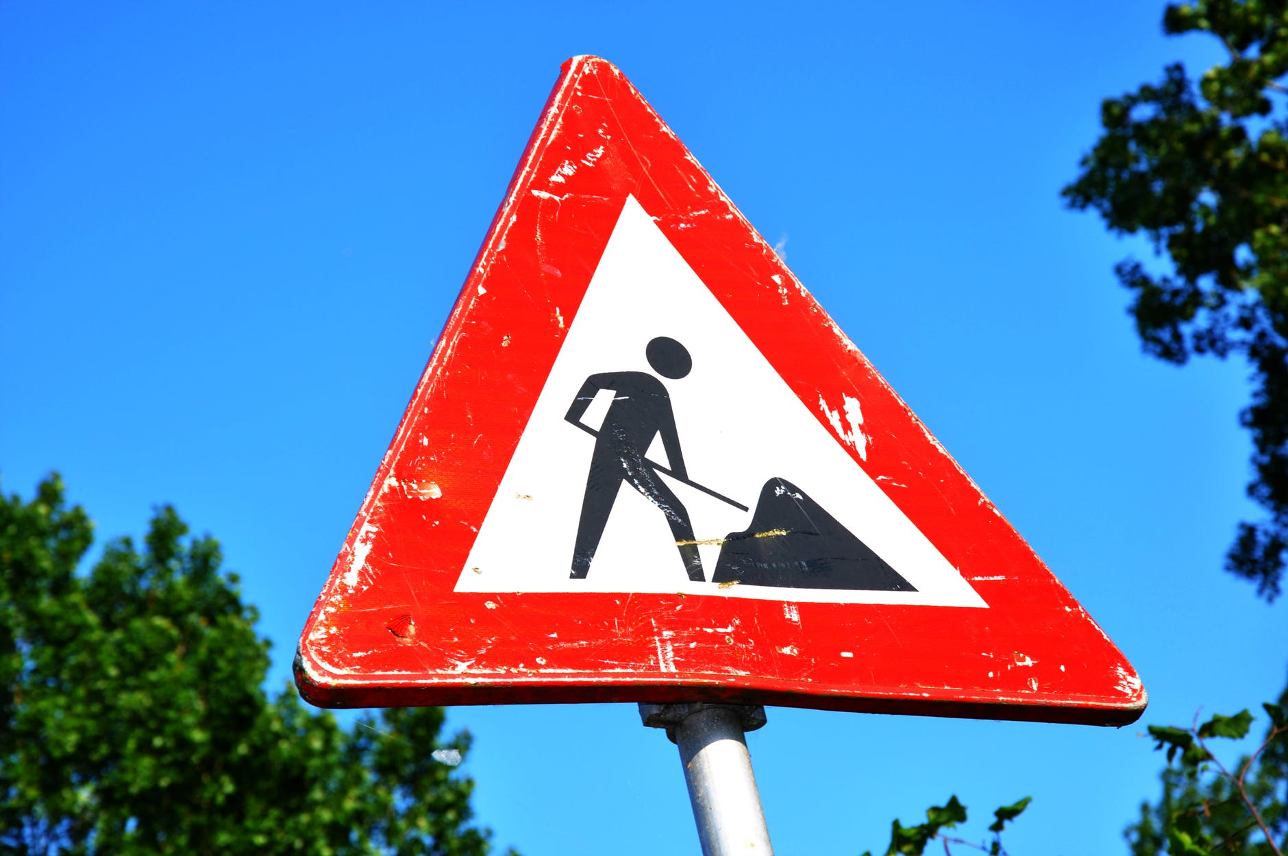 A white triangle-shaped road work sign depicting a human shoveling dirt is outlined in red