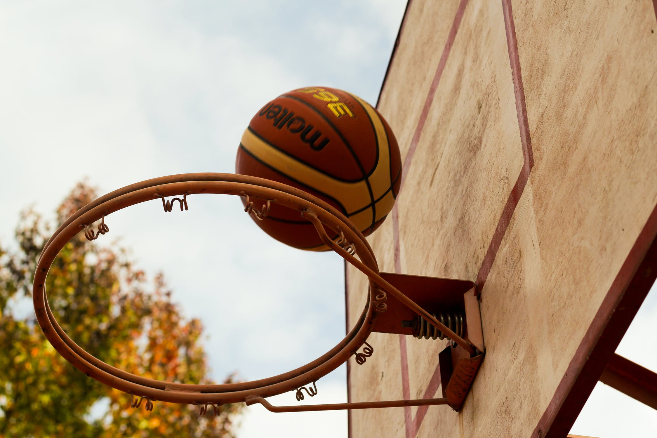 A basketball hovers over the rim of a basketball hoop