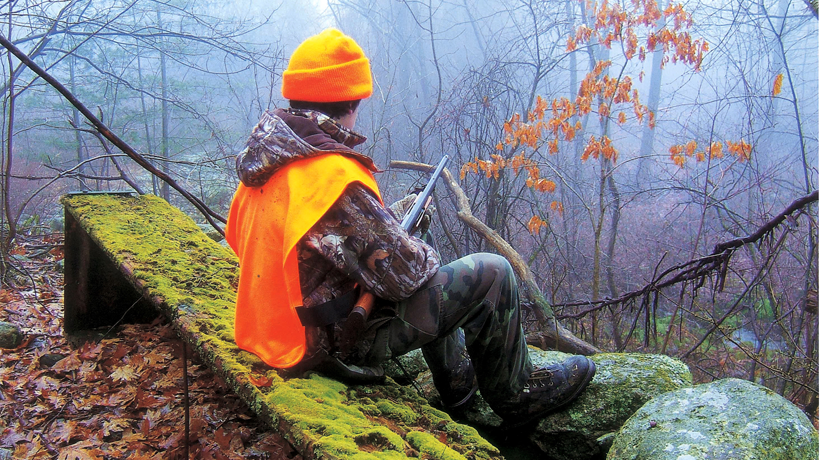 A hunter wearing blaze orange sits on a log