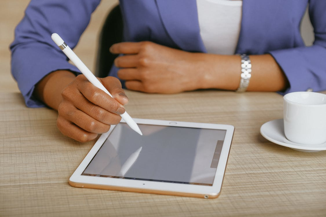 A person uses a pencil to take a survey on a tablet
